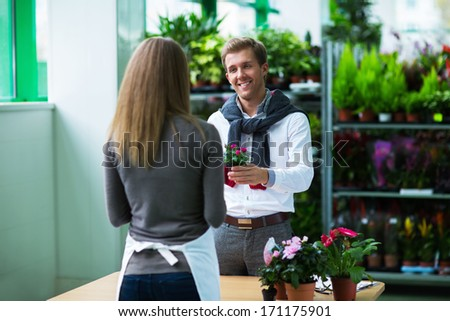 Saleswoman and customer at the store flowers - stock photo