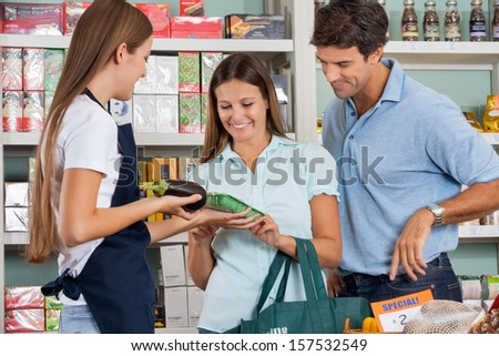 Saleswoman assisting couple in buying groceries at supermarket - stock photo