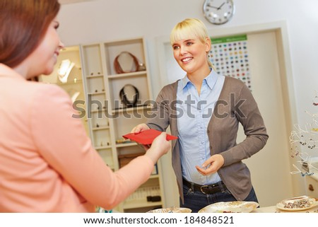 Saleswoman behind counter handing jewelry to customer in a store - stock photo