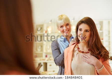 Saleswoman helping woman fitting a necklace in a jewelry store - stock photo