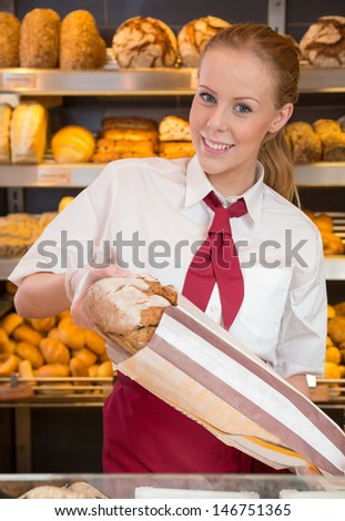 Saleswoman in bakery putting loaf of bread into plastic bag for a customer
