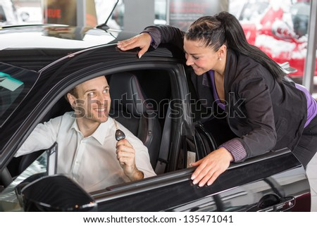 Saleswoman in car dealership selling a automobile - stock photo