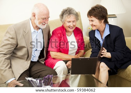 Saleswoman meets with senior couple in their home.  Could be real estate, life insurance, etc. - stock photo