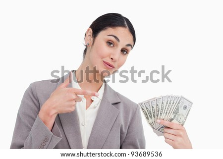 Saleswoman pointing at bank notes in her hand against a white background