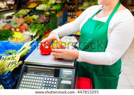 Saleswoman weighting vegetables on scale in grocer - stock photo
