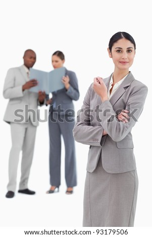 Saleswoman with co-workers behind her against a white background