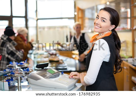 Saleswoman working at cash register or checkout counter in shop - stock photo