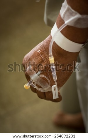 Saline intravenous solution in a patients hand  - stock photo