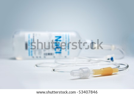 Saline IV drip on blue background in shallow depth of field - stock photo