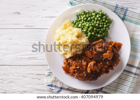 Salisbury steak with gravy, mashed potatoes and green peas close-up on a plate on the table. horizontal top view 