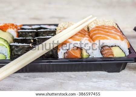 Salmon and avocado sushi in a black tray
