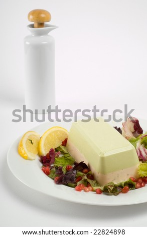 Salmon and avocado terrine on white plate with salad and oil dressing - stock photo