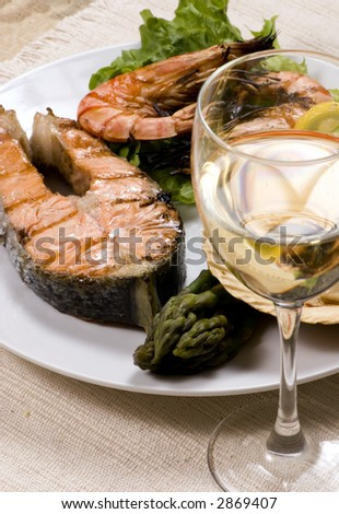 Salmon and shrimp dinner with white wine - stock photo