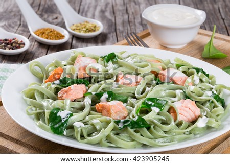salmon and spinach fettuccine pasta on white dish and table napkin, cream sauce in a gravy boat, spices in porcelain spoon on wooden italian style, top view  - stock photo