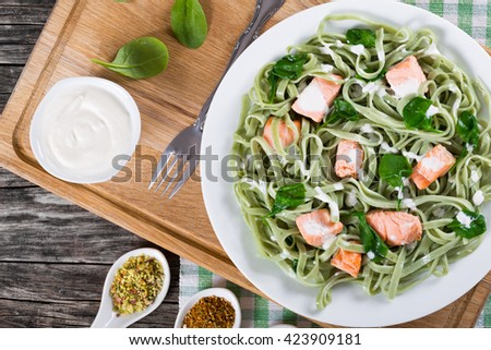 salmon and spinach fettuccine pasta on white dish and table napkin, cream sauce in gravy boat, spices and pistachios in porcelain chinese style spoon on a wooden top view  - stock photo