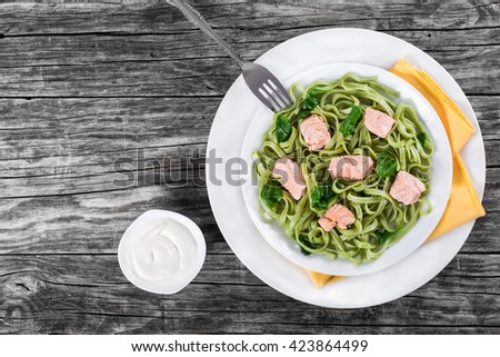 salmon and spinach fettuccine pasta on white dishes and table napkin. cream sauce in a gravy boat on a italian style, top view  - stock photo