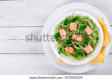 salmon and spinach fettuccine pasta on white dishes and table napkin on a italian style, top view  - stock photo