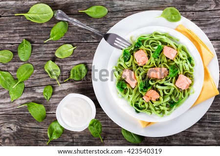 salmon and spinach fettuccine pasta on white dishes with fork and napkin, cream sauce on a gravy boat on a table, italian style, top view  - stock photo