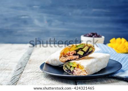 Salmon avocado mango black rice burritos. toning. selective focus - stock photo