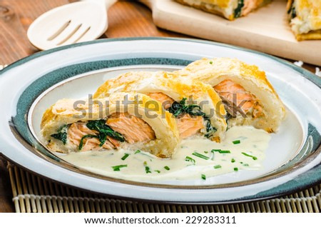 Salmon baked in puff pastry with spinach and garlic - stock photo