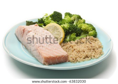 Salmon, broccoli, couscous, and a slice of lemon on an aqua colored plate, on white background - stock photo
