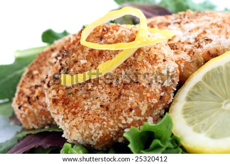 Salmon cakes on bed of lettuce with lemon - stock photo