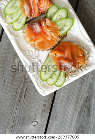 Salmon Canapes. Small sandwiches with salmon and cucumber. copy space - stock photo
