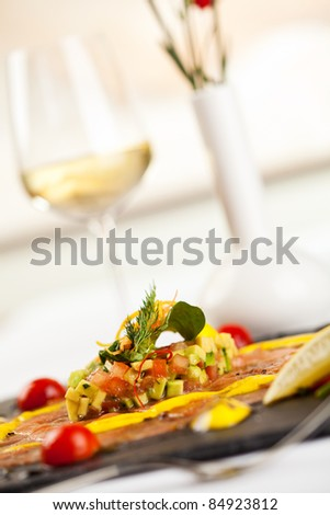 Salmon Carpaccio on Black Dish with White Wine - stock photo