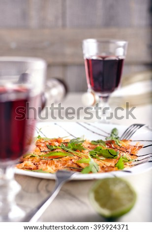 Salmon carpaccio with arugula leaves, lime juice sticky balsamic vinegar two glasses of wine and two forks on wooden background. - stock photo