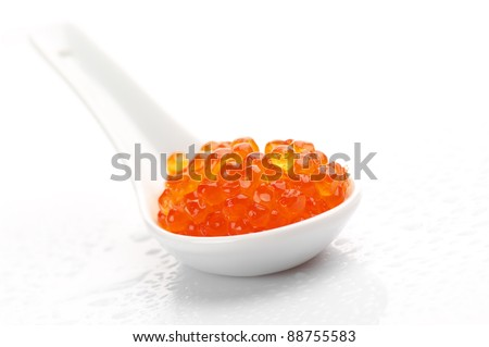 Salmon caviar in white ceramic spoon on white background. - stock photo