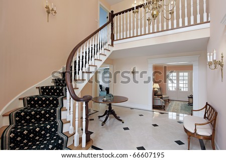 Salmon colored foyer with curved staircase and carpeted stairs - stock photo