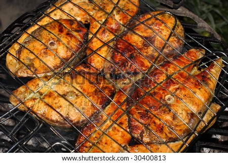 Salmon cooking on grill - stock photo