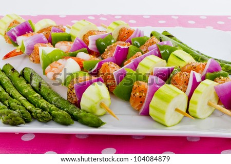 Salmon cubes and Shrimp complimented with vegetables on skewers. Ready to cook. Red onions, zucchini, green peppers and asparagus. - stock photo