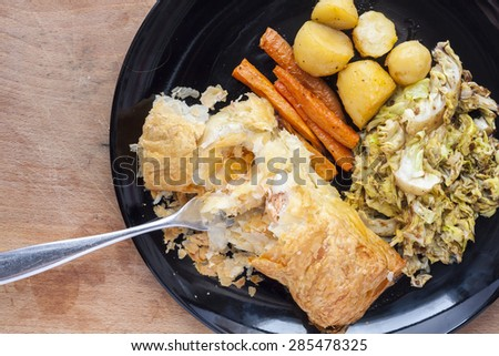 Salmon en croute, with vegetables, served on a black plate - stock photo