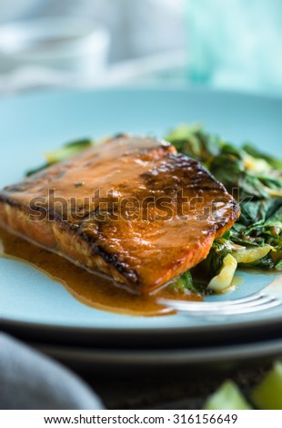 Salmon filet roasted with red curry sauce and sauteed greens - stock photo