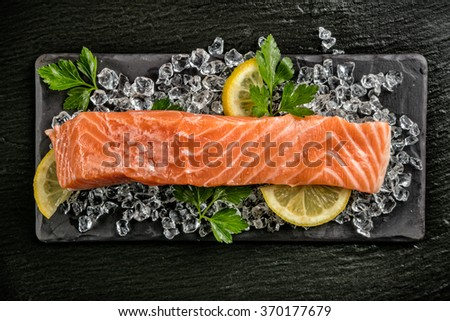 Salmon filet served on black stone - stock photo