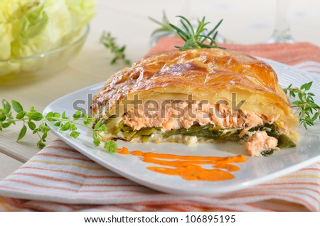 Salmon fillet on leek, baked in puff pastry - stock photo