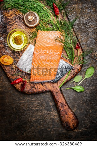 Salmon fillet on old cutting board with oil, herbs and spices, top view, close up - stock photo