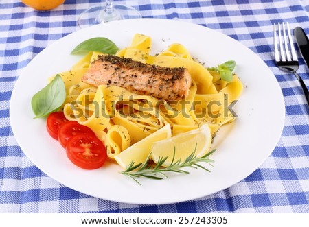 Salmon fillet on tagliatelle, herbs, lemon, top view - stock photo