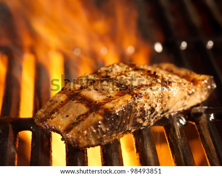 salmon fillet on the grill with flames in horizontal orientation - stock photo
