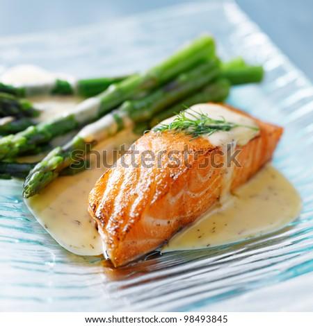 Salmon fillet with asparagus and yellow sauce closeup - stock photo
