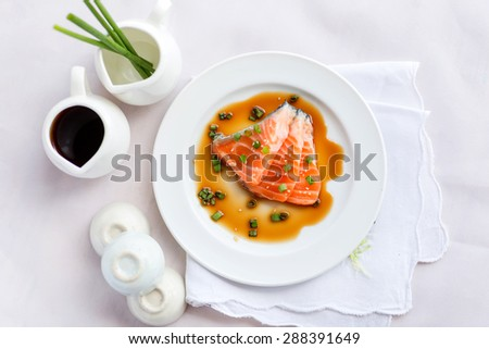 salmon fillet with sauce on white dish - stock photo