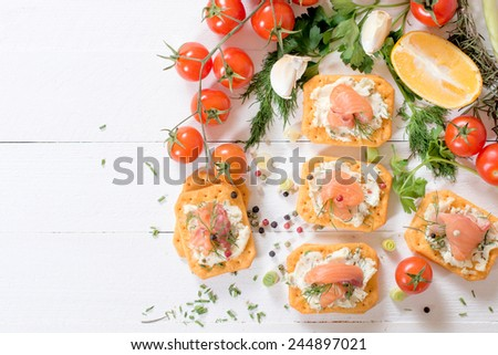 Salmon fillets and cream cheese on crackers from above,selective focus  - stock photo
