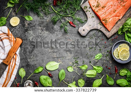 Salmon fish fillets on cutting board and fresh ingredients for cooking on rustic background, top view frame. Healthy or diet food concept. - stock photo