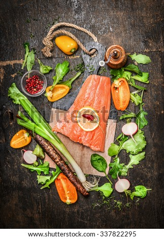 Salmon fish fillets on cutting board with fresh vegetables and spices ingredients on rustic wooden background, top view. Healthy clean food or diet cooking concept.  - stock photo