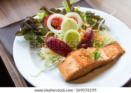 Salmon fish steak with  Vegetable salad on plate.