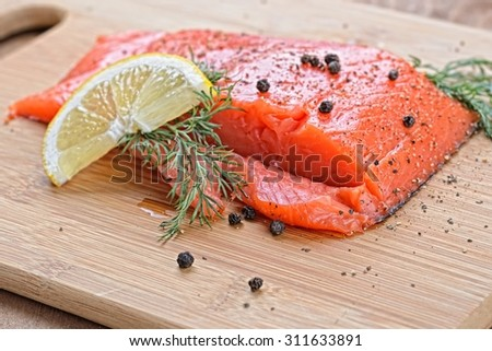 salmon fish with fresh herbs, pepper and lemon  - stock photo