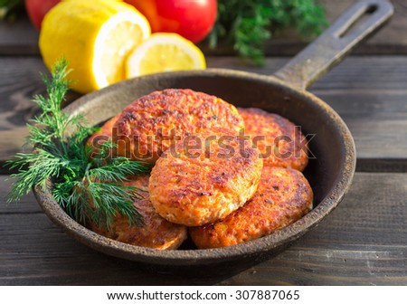 salmon fishcakes in a cast iron skillet, tomatoes and lemon on a dark table. Selective focus - stock photo