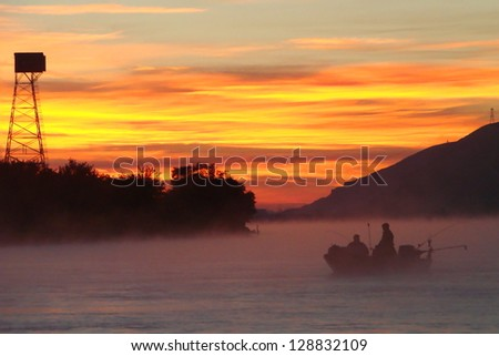 Salmon fishing boat on the Columbia River at sunrise in morning fog, Washington state trout fly fishing trolling motor boat Pacific Northwest foggy mist silhouette - stock photo