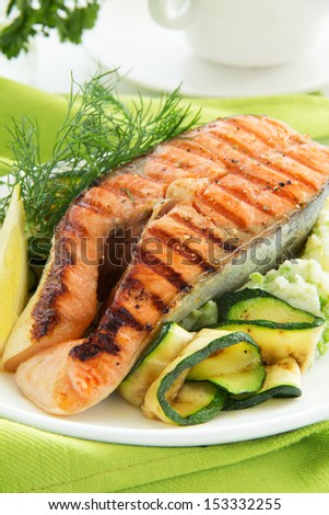 Salmon fried on a grill with zucchini.